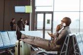 podnikatel mluví po telefonu při čekání na letadlo v letištní hale
