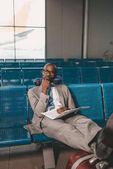 Fotografie znuděného podnikatele s cestovní polštář čekání na letadlo v letištní hale