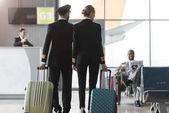 Fotografia vista posteriore di piloti maschili e femminili a piedi dalla hall dellaeroporto con le valigie