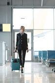 Krásné ženské pilot s kufrem walking v letištní hale