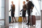 Fotografia pilota e hostess con bagagli a piedi nelle vicinanze aeroporto