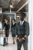Fotografia bello giovane pilota in aeroporto con hostess prima del volo
