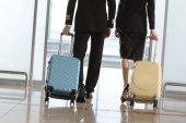 oříznuté záběr pilot a letuška s kufry chůze u letiště