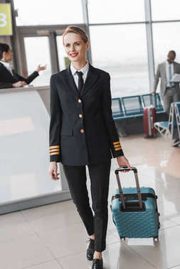 female pilot with suitcase walking by airport lobby