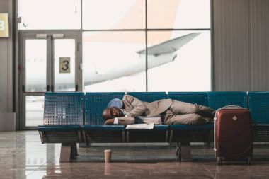 Exhausted businessman sleeping on seats while waiting for flight at airport lobby stock vector