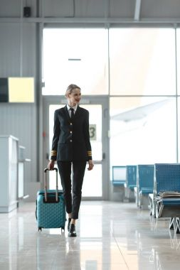 beautiful female pilot with suitcase walking by airport lobby