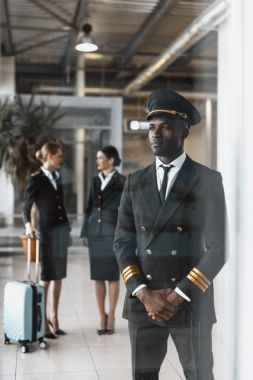 handsome young pilot in airport with stewardesses before flight