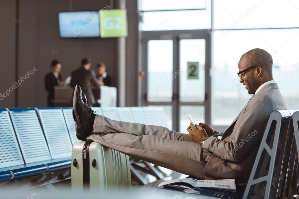 smiling businessman using smartphone while waiting for flight at airport lobby