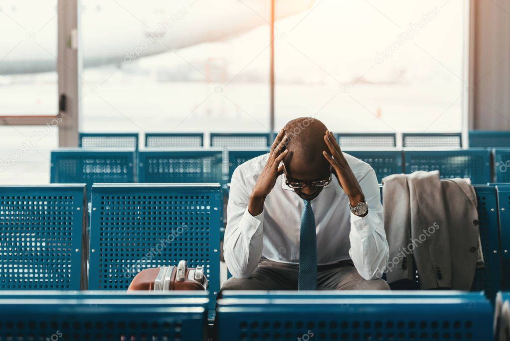 tired businessman waiting for flight at airport lobby