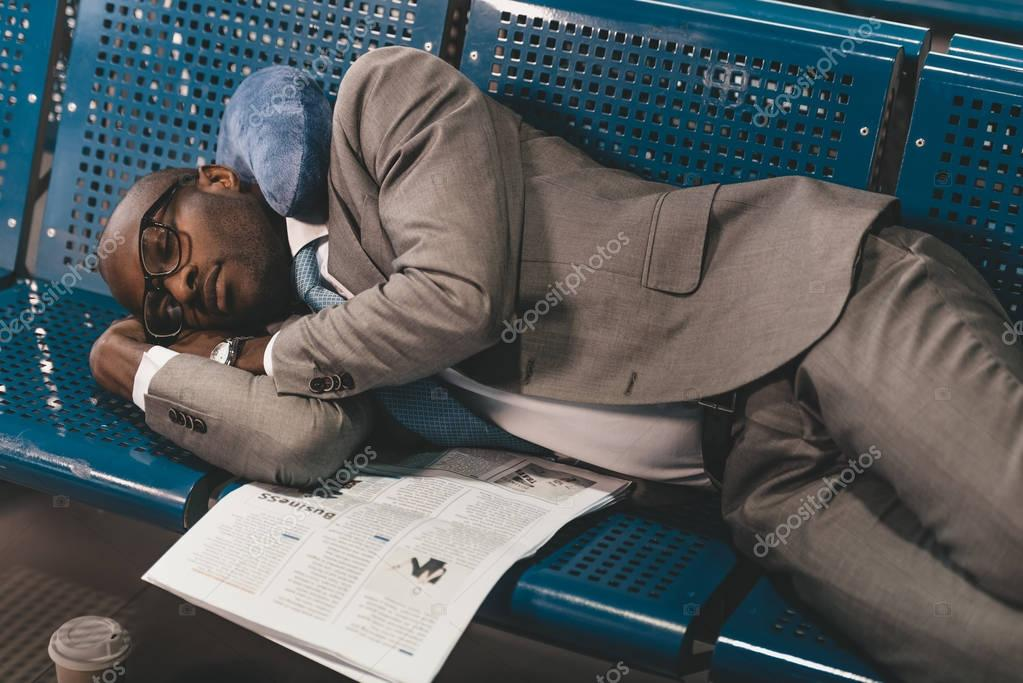 tired businessman sleeping on seats while waiting for flight at airport lobby
