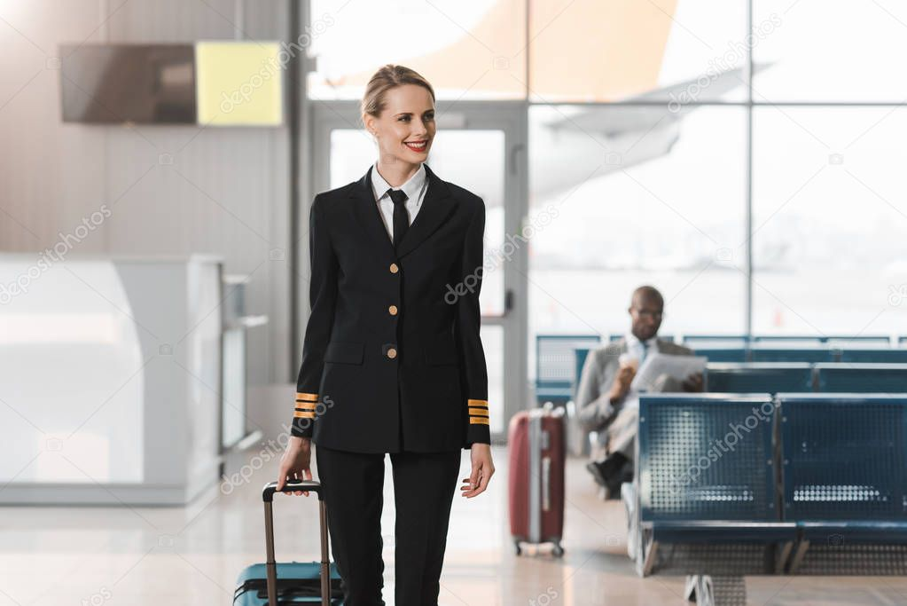smiling female pilot with suitcase walking by airport lobby