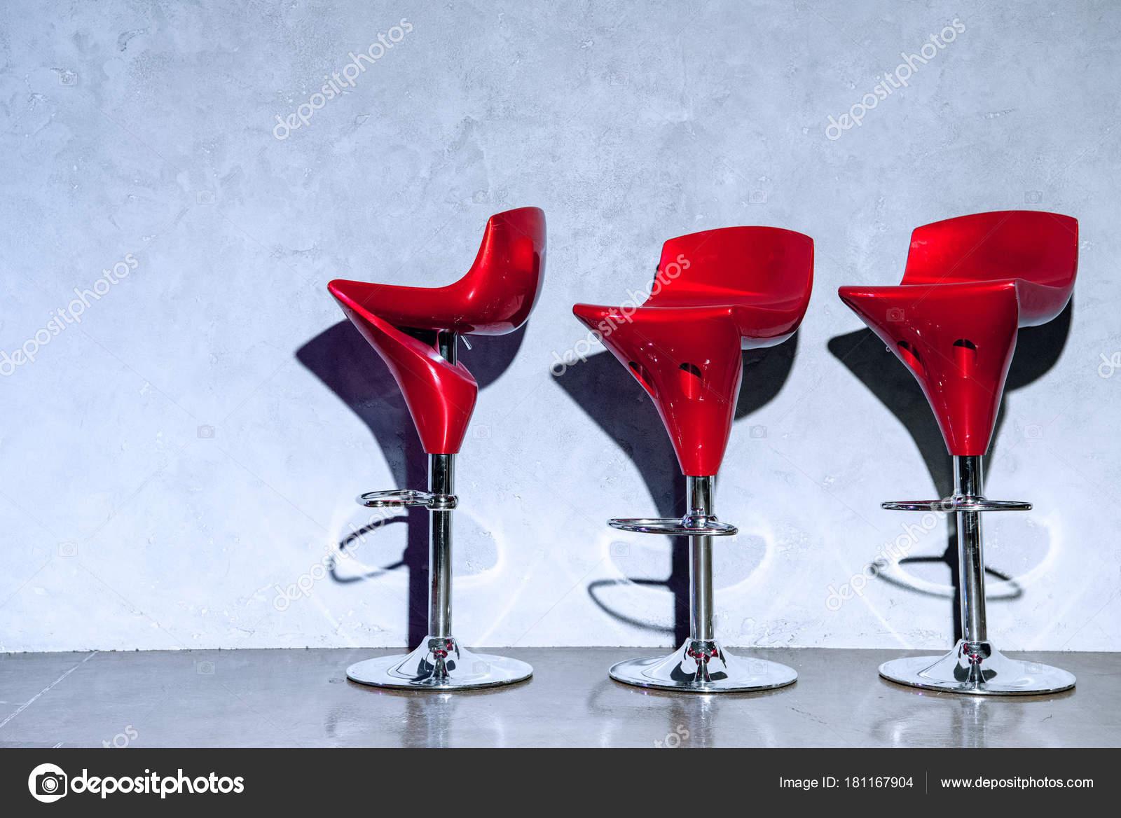 Tre rosso vuoto bar sgabelli vicino alla parete grigia u2014 foto stock