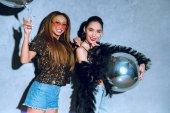 beautiful stylish multiethnic women holding balloons and smiling at camera