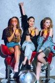 Fotografie schöne modische multiethnischen Frauen sitzen auf Barhockern und tranken Cocktails auf party