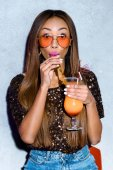 Photo beautiful fashionable african american girl drinking cocktail and looking at camera