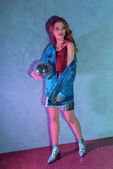 Fotografie fashionable young woman holding disco ball and looking away on grey