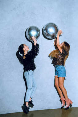 side view of fashionable young women having fun with shiny silver balloons