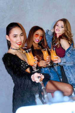 stylish multiethnc girls drinking cocktails and taking selfie with smartphone at party