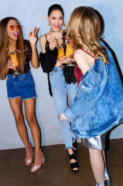 beautiful happy stylish multiethnic girls drinking cocktails and talking at party