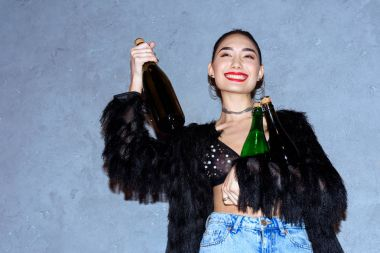 fashionable happy asian girl holding bottles with alcoholic beverages on grey