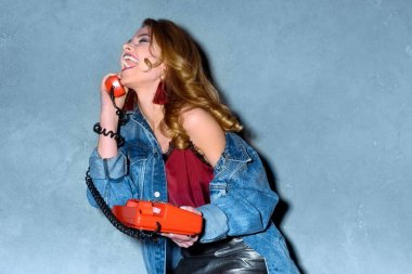 happy young woman talking on retro telephone against concrete wall