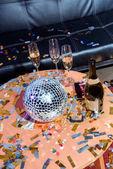 Fotografie zblízka pohled šampaňského a disco koule na stole v místnosti stran