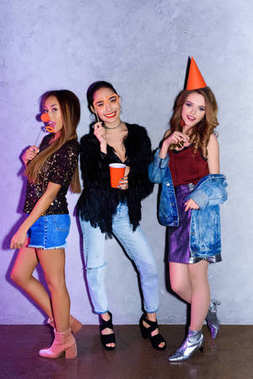 happy multiethnic young women with party decorations against concrete wall