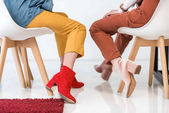 Fotografie cropped view of stylish women in trendy shoes sitting on chairs