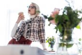 Fotografie attractive fashionable businesswoman with coffee to go in modern office