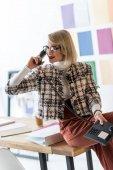 Módní podnikatelka mluví o telefonu v moderní kanceláři s barevnou paletu na zdi