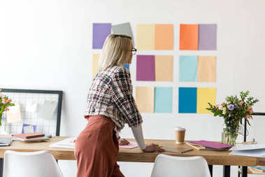 rear view of fashion magazine editor working in modern office with color palette on wall