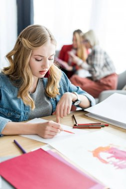 young blonde magazine editor drawing sketches in modern office, colleagues sitting behind