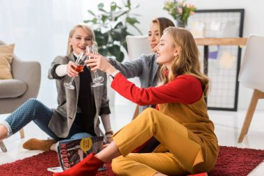 successful fashionable businesswomen celebrating and clinking with champagne glasses in office