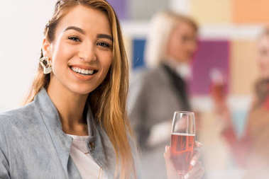 cheerful asian girl celebrating with glass of champagne in modern office