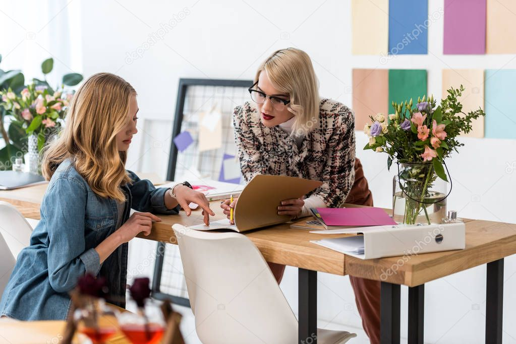 fashionable magazine editors doing paperwork in modern office with color palette