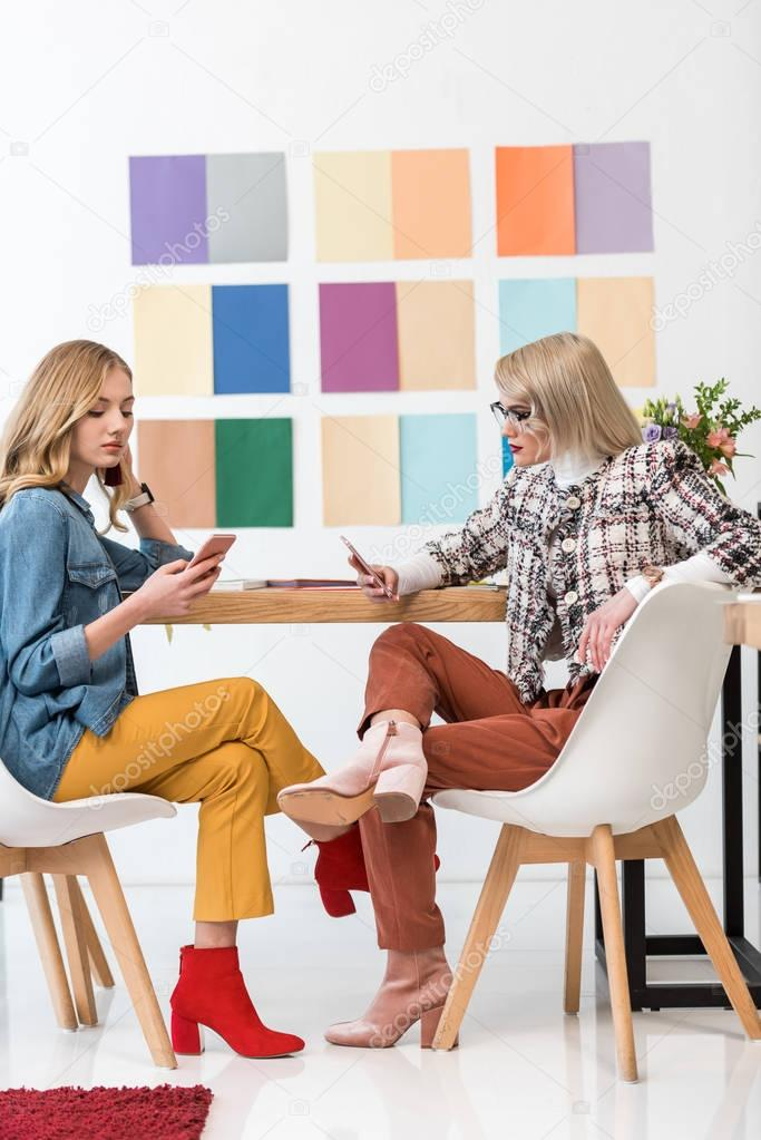 magazine editors working with smartphones at workplace with color palette on wall