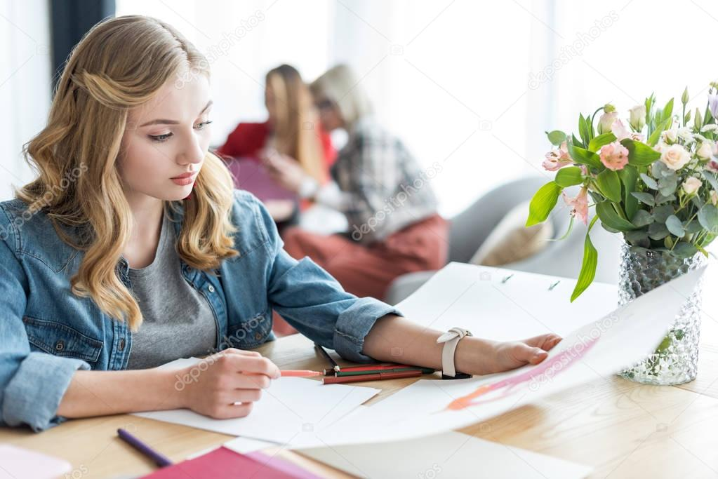 beautiful magazine editor drawing sketches in modern office, coworkers sitting behind