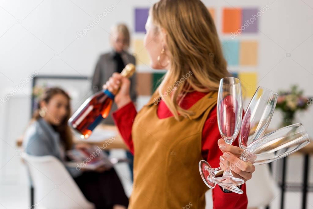 magazine editors celebrating triumph with champagne in modern office
