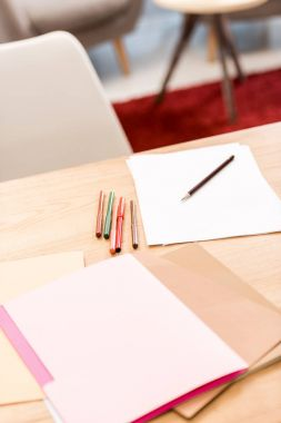 documents and folders with markers on table in office