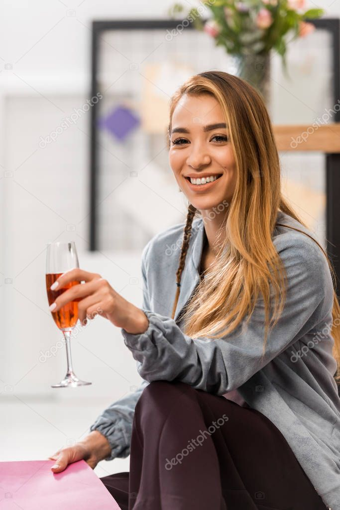 asian girl celebrating with glass of champagne in modern office
