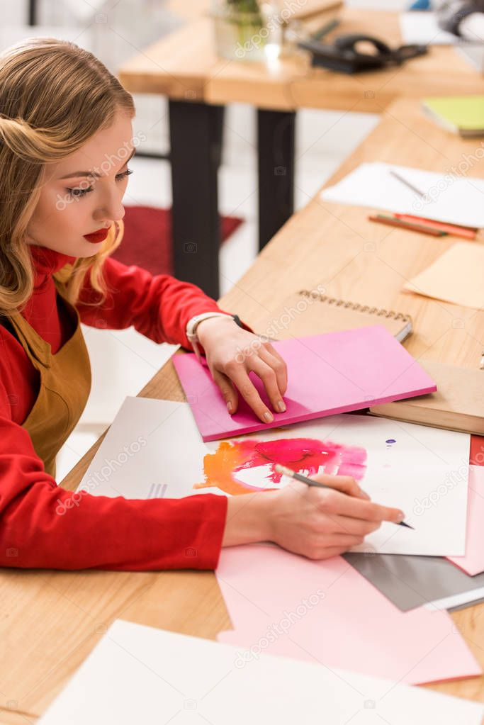 attractive fashion magazine editor working with sketches and documents in modern office