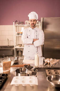 young confectioner with arms crossed standing at counter in restaurant kitchen