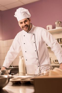 young happy confectioner standing at counter in restaurant kitchen