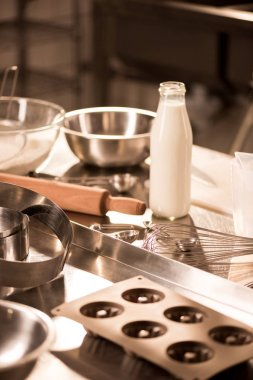 close up view of ingredients for dough and kitchen utensils on counter in restaurant