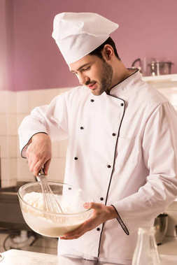 young confectioner in chef hat making dough in restaurant kitchen