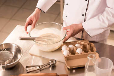 partial view of confectioner adding raw egg into dough in restaurant kitchen