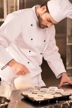 portrait of confectioner pouring dough into baking forms in restaurant kitchen
