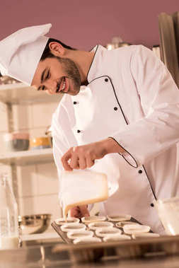 smiling confectioner pouring dough into baking forms in restaurant kitchen