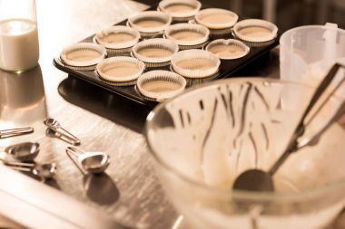 close up view of baking forms with raw dough for cupcakes