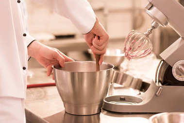 partial view of confectioner making cream for dessert in restaurant kitchen